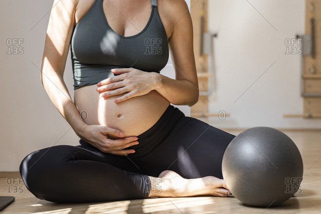 Unrecognizable pregnant woman in sportswear sitting on the fitness studio floor.