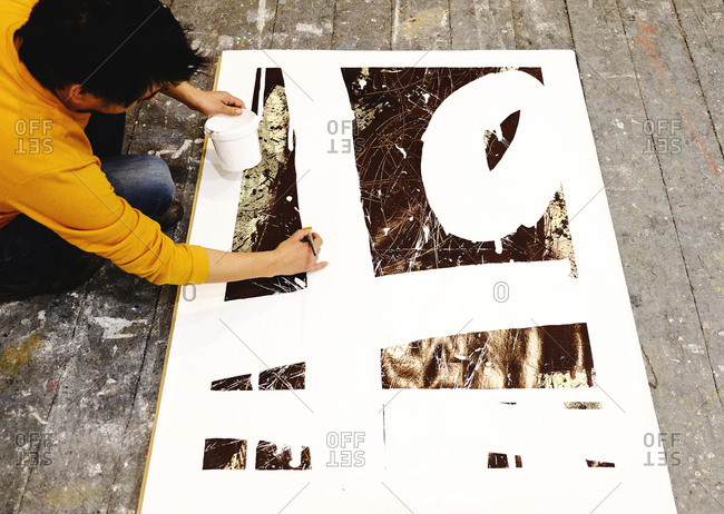 Overhead view of an artist painting a large picture on workshop floor