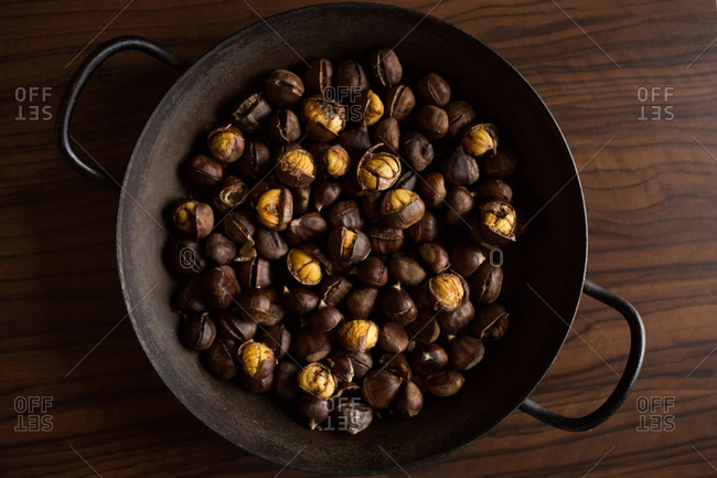 Chestnuts in a wok on a wooden surface