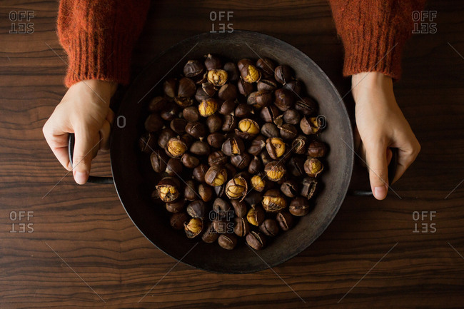 Overhead view of woman holding a wok filled with chestnuts
