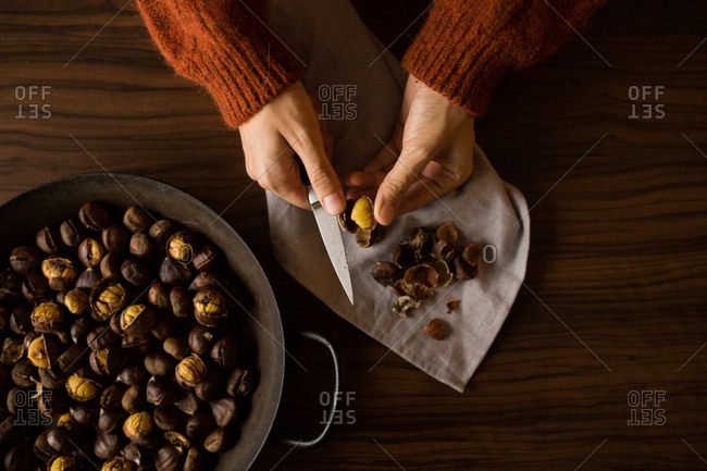 Woman using knife to cut shell off of chestnuts
