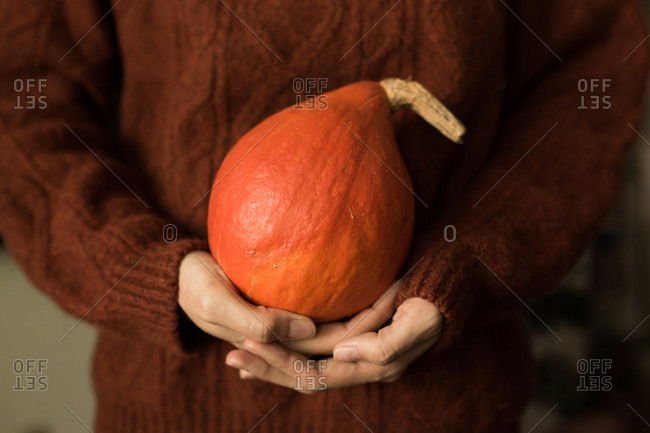 Woman holding a whole orange winter squash
