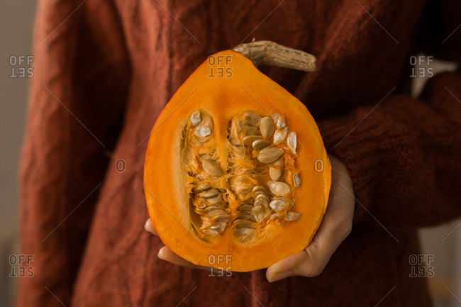 Woman holding half of an orange winter squash