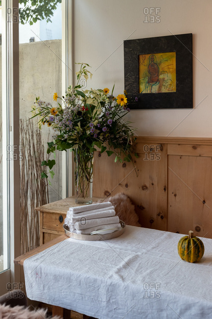Meran, South Tyrol, Italy - October 1, 2019: Tray with rolled towels on a table beside a fall floral arrangement