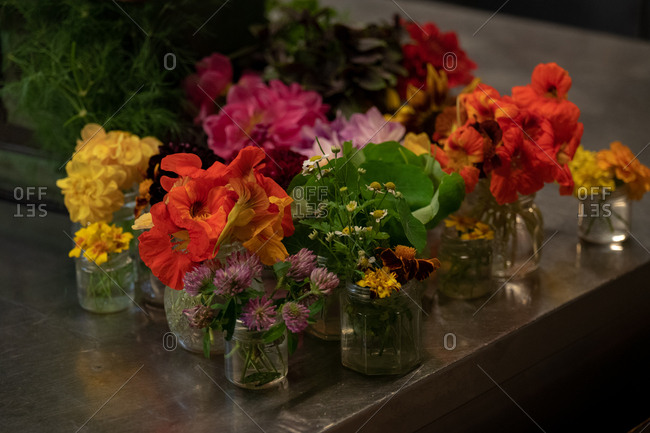 Small jars with a variety of colorful flowers