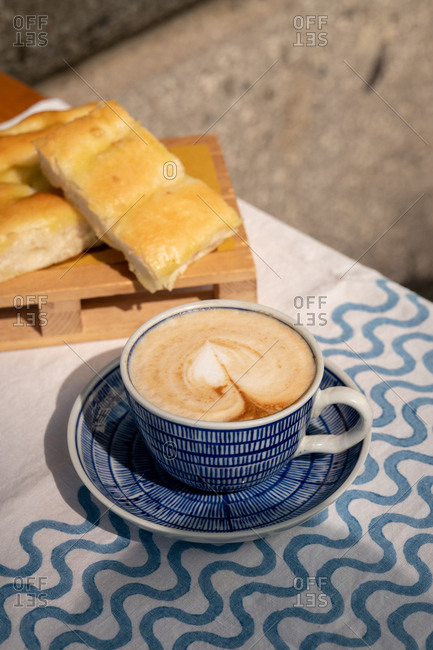 A cappuccino and focaccia on an outdoor table