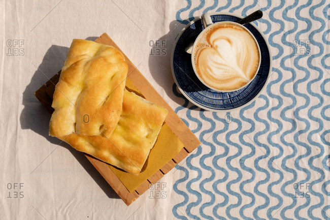 Overhead view of a cappuccino and focaccia on an outdoor table