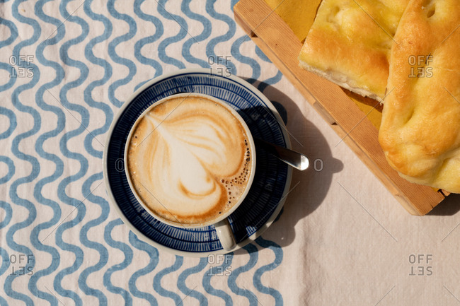 Overhead view of a cappuccino beside focaccia on an outdoor table