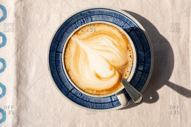 Overhead view of a cappuccino on an outdoor table