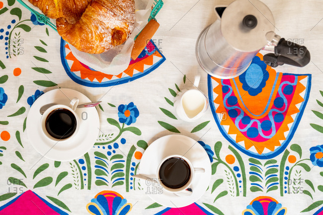 Overhead view of croissants, coffee and a moka pot on a colorful background