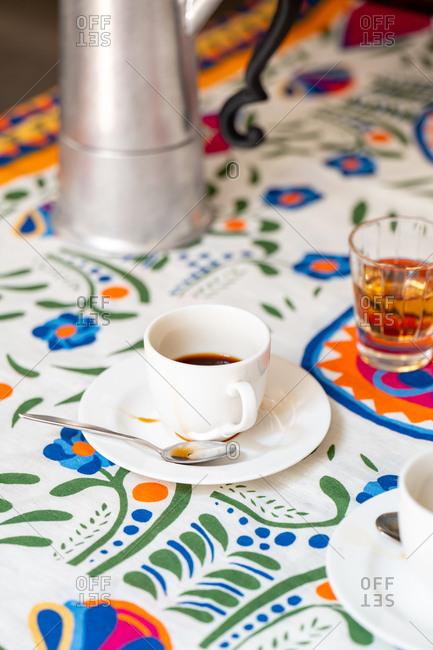 Close up of coffee amaro beside a moka pot