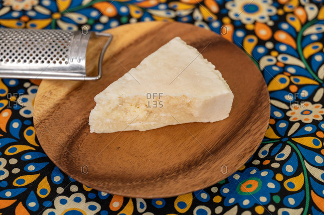 A wedge of parmesan cheese on a wooden board