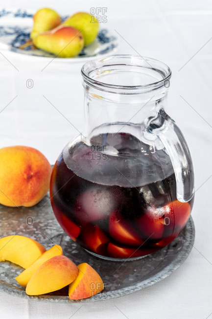 Peach sangria in a pitcher beside a plate with pears