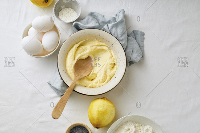 Mixing butter and sugar with wooden spoon while cooking lemon cake