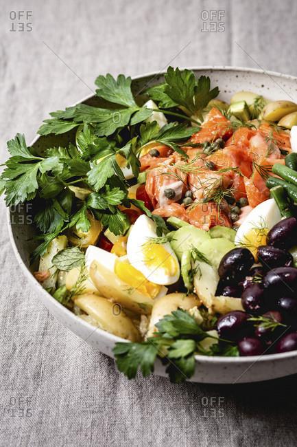 Salmon Nicoise salad on a neutral grey table cloth.
