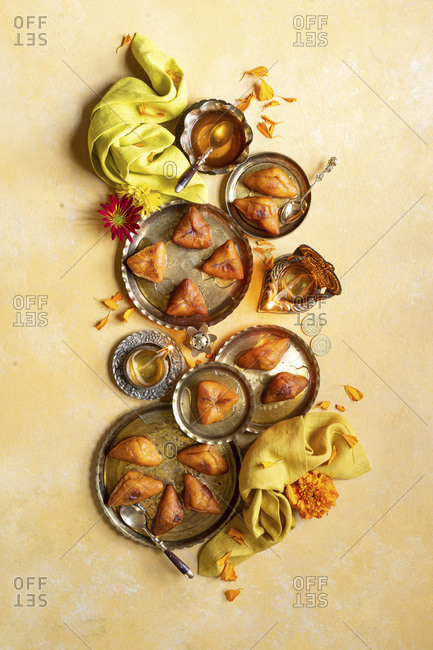 Diwali Special - Sweet Potato Dumplings with Indian traditional brass candles, yellow napkin, flowers.