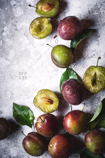 Whole And Sliced Plums With Water Droplets And Leaves