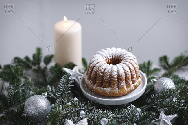 Mini bundt cake sprinkled with powdered sugar on a little cake stand