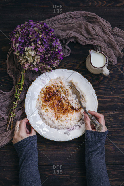 Woman eating rice pudding sprinkled with sugar and cinnamon