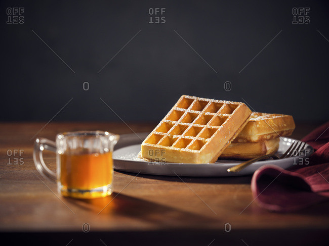 A plate with 3 belgian waffles with powdered sugar. Pitcher of maple syrup in the foreground. Warm, moody lighting on wood tabletop.