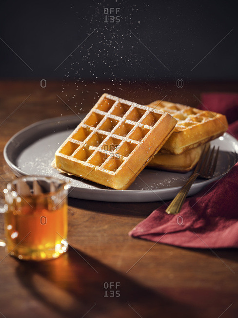 A plate with 3 belgian waffles being sprinkled with powdered sugar. Pitcher of maple syrup in foreground. Warm, moody lighting on wood tabletop.