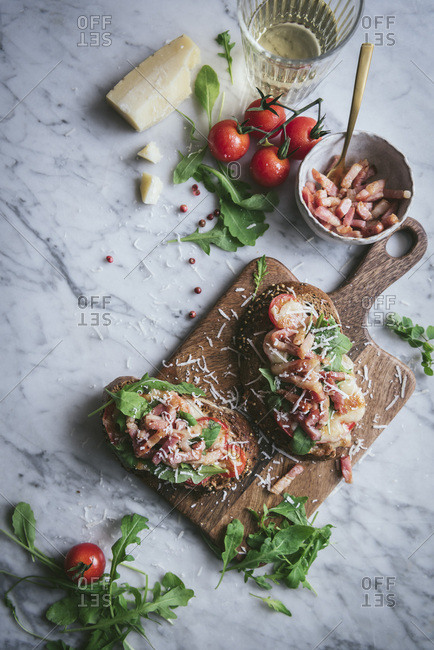 Bacon toasties on a chopping board in a rustic kitchen