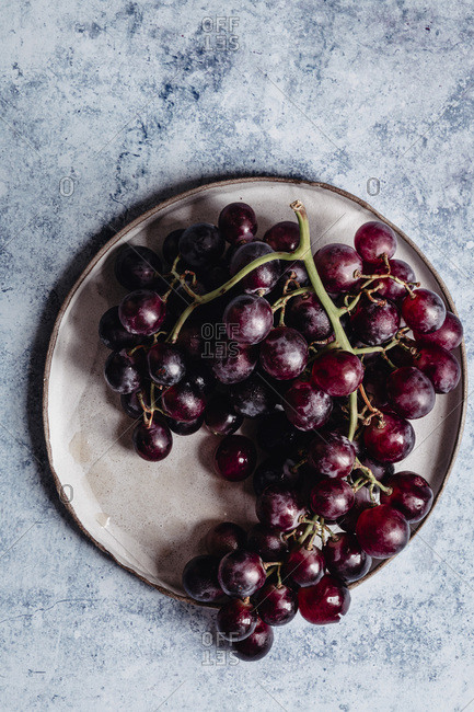 Red grapes on a light blue backdrop