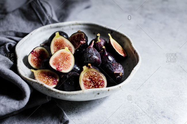 Halved figs in a bowl on a white background