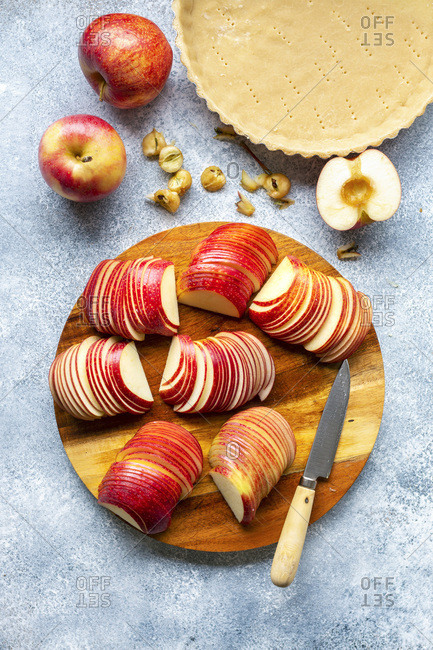 Preparation of an apple tart. Sliced apples on a wooden board