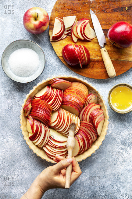 Preparation of an apple tart. Hand brushing sliced apples with melted butter
