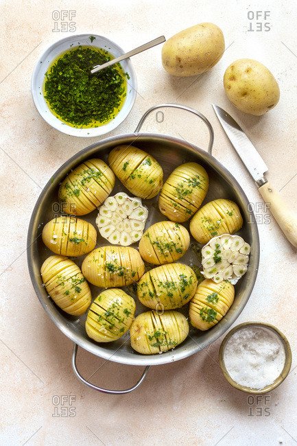 Preparing hasselback potaoes. Sliced potatoes drizzled with parsley dressing ready to bake.