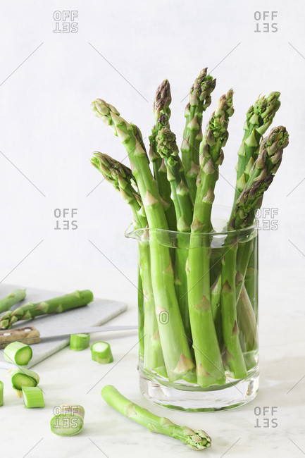 Trimmed asparagus stems in a jug of water.