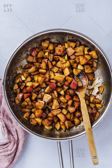 Cooking spiced diced apples with butter and brown sugar in a pan.