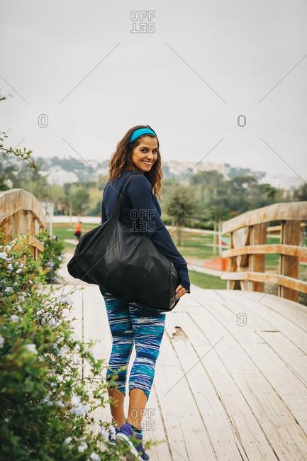 Portrait confident female personal trainer walking over footbridge in park