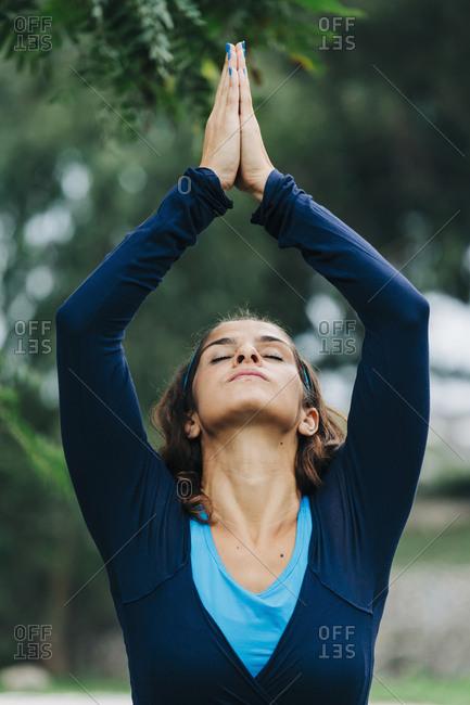 Serene woman practicing yoga in park