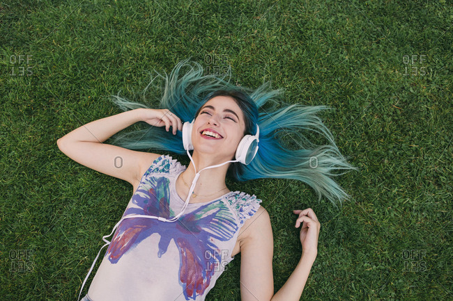 Happy, carefree young woman with blue hair listening to music with headphones, laying in grass