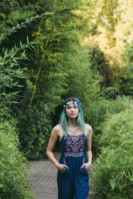 Portrait young woman with blue hair on footpath in lush park