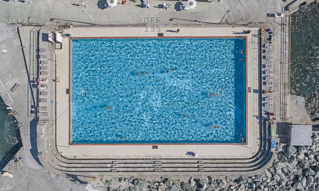 Aerial view from above tourists swimming in sunny, blue resort swimming pool, Genoa, Liguria, Italy