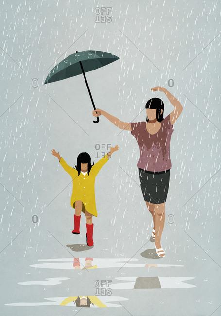 Carefree mother and daughter dancing in rain