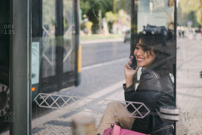 Happy young woman talking on smart phone at bus stop