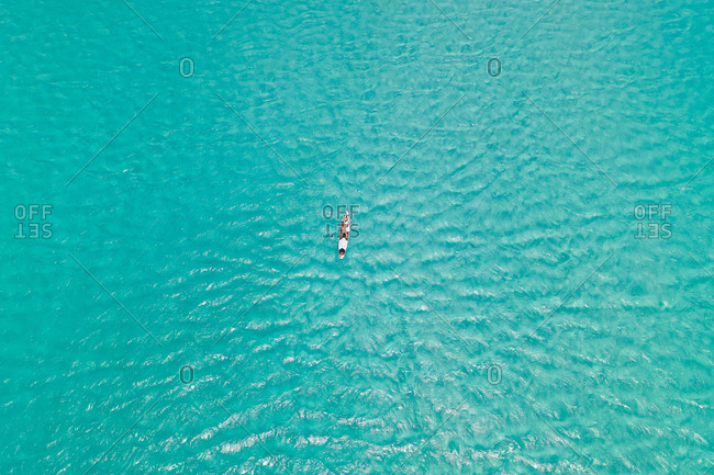 Aerial view of woman practicing standup paddle over transparent water, South Africa.