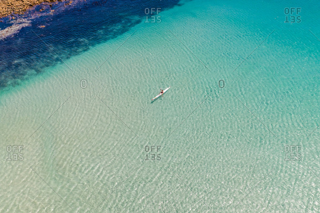 Aerial view of man with kayak over transparent water, South Africa.