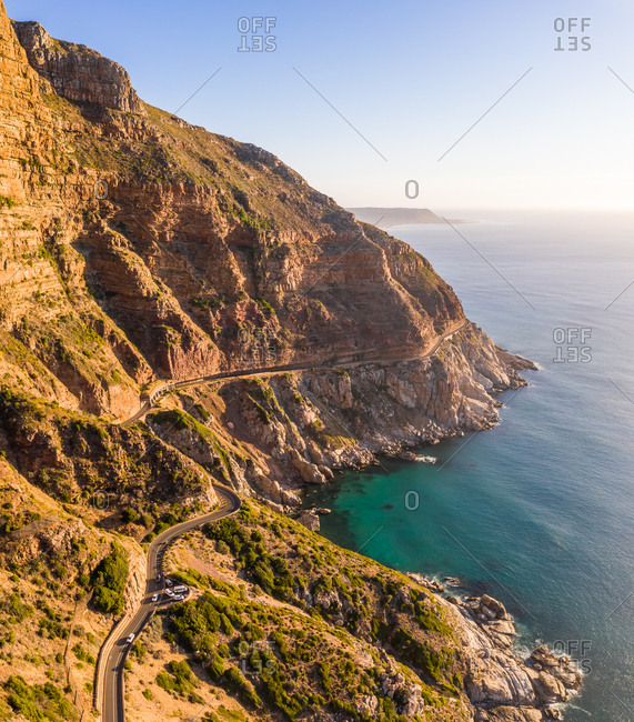 Aerial view of road zigzagging at Chapmans Peak during sunset, South Africa.