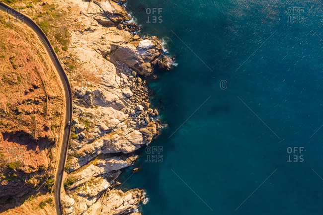 Aerial view above of road zigzagging at Chapmans Peak during sunset, South Africa.