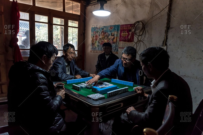 March 14, 2019: Group of elderly Chinese men playing mahjong in Yunnan, China