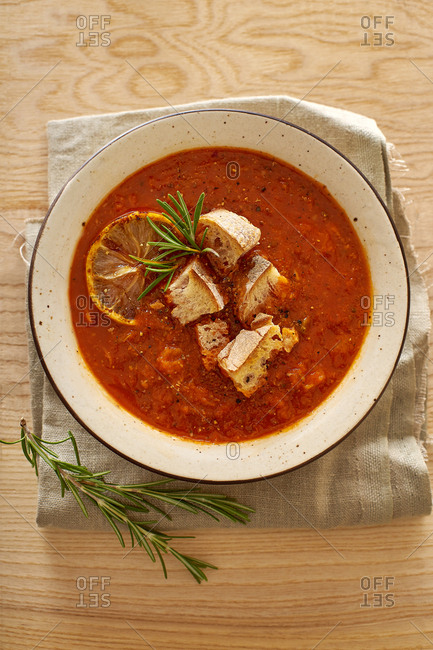 Tomato vegetable warm soup on wooden table served with ciabatta croutons. Comfort food