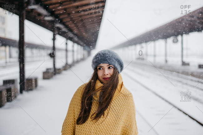 Beautiful young brunette wearing yellow poncho and a winter cap among snowy scenery at a railway station