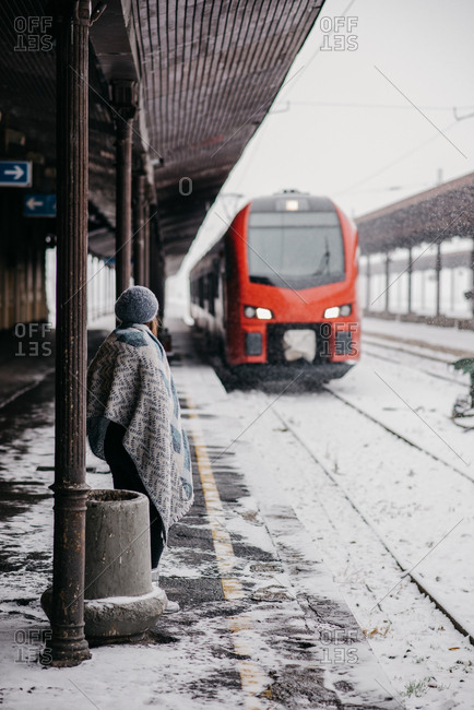 Arriving train and a woman waiting at a railway station in winter