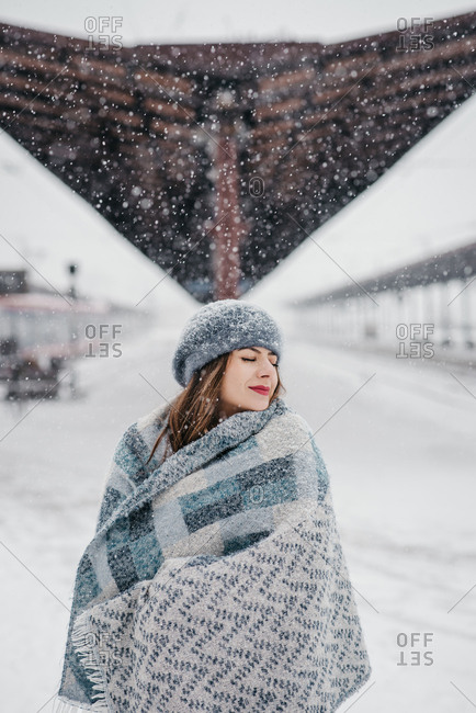 Beautiful young woman enjoying among beautiful snowflakes in winter