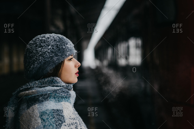 Portrait of a young woman covered in snow waiting for a train